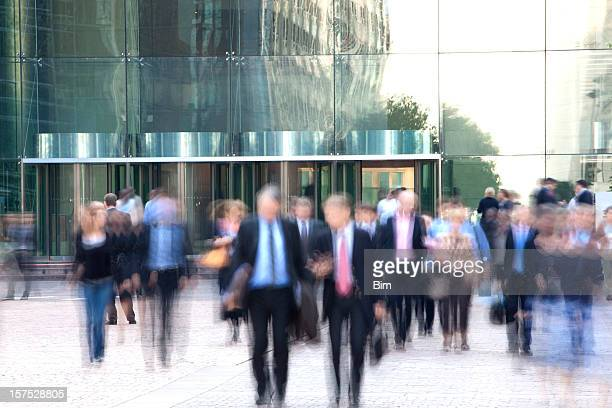 Business people walking out of an office building, blurred motion