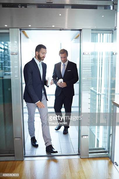 Business people walking out of elevator