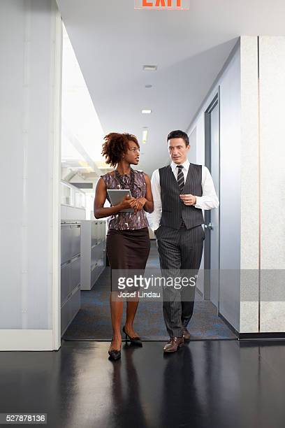 business people walking through corridor and talking - overhemd en stropdas stockfoto's en -beelden