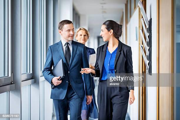 Business people walking through corridor and talking