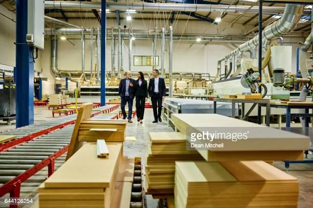pessoas de negócios andando através da linha de produção da fábrica - mobília - fotografias e filmes do acervo