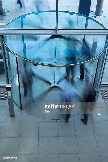 Business People Walking Through Glass Revolving Door