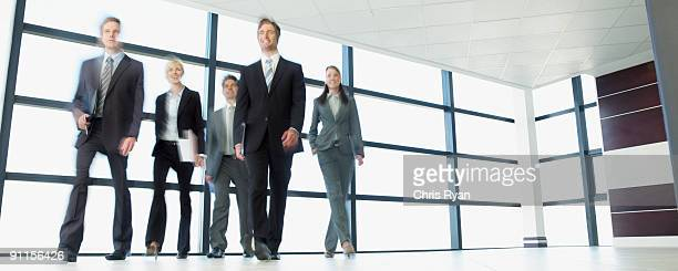 business people walking through office lobby - five people stock pictures, royalty-free photos & images