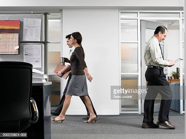 Business people walking through office, side view