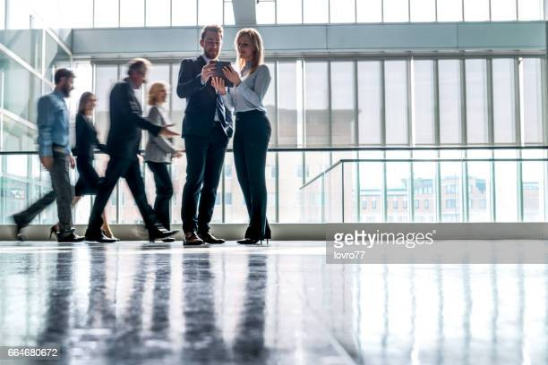 business people walking through the lobby. - medium group of people stock pictures, royalty-free photos & images