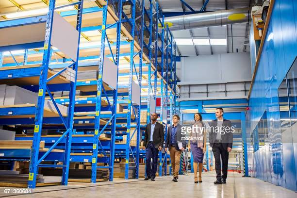 business people walking through warehouse - bezoek stockfoto's en -beelden
