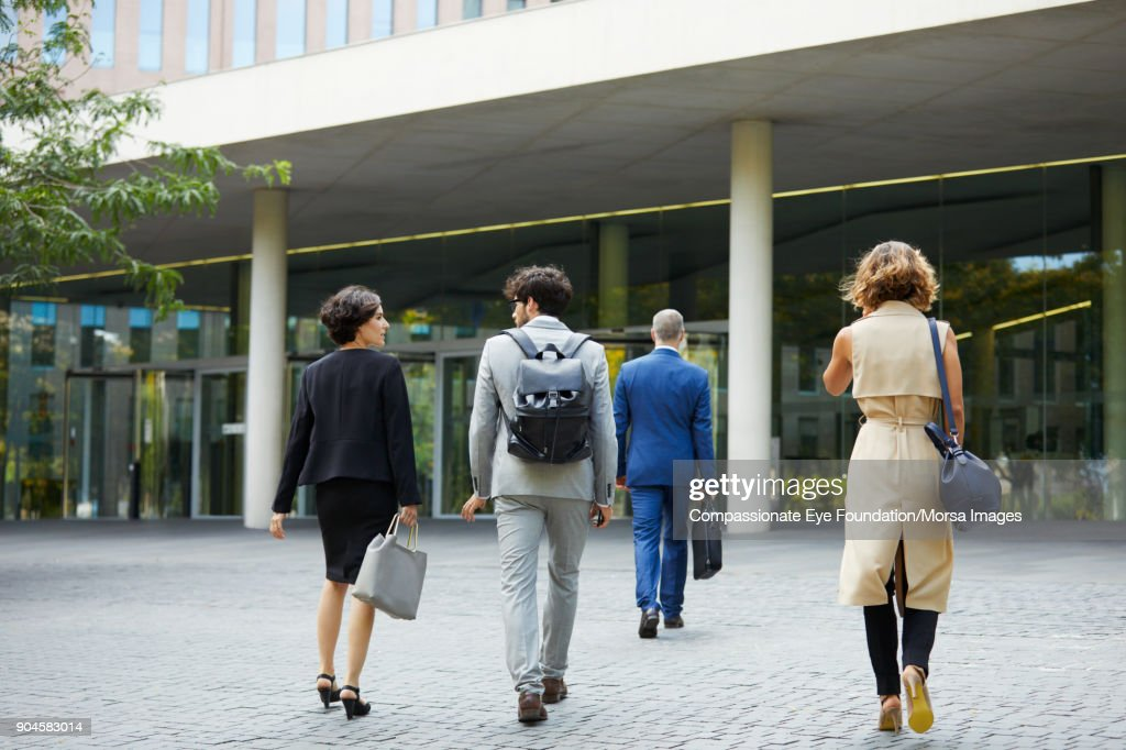 Business people walking towards office building : Stock Photo