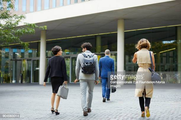 business people walking towards office building - arrival stock pictures, royalty-free photos & images