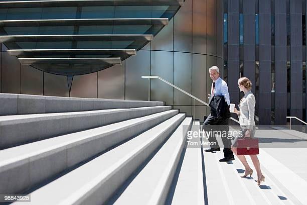 business people walking up steps - steps stock photos and pictures