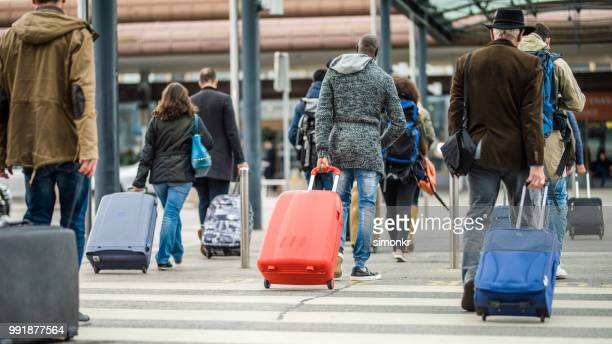 business people walking with wheeled luggage - red coat stock pictures, royalty-free photos & images