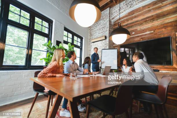 business people watching a presentation on the whiteboard - wide angle stock pictures, royalty-free photos & images