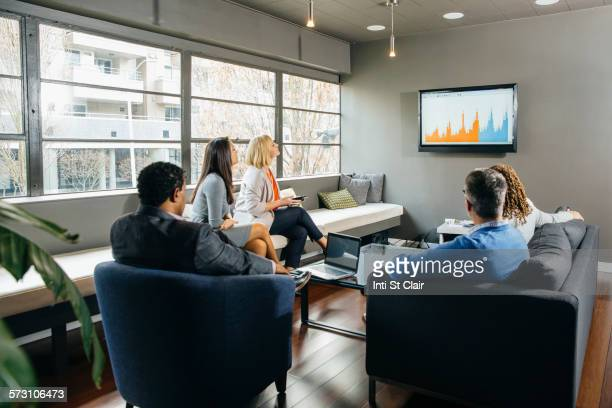 Business people watching presentation in office lounge