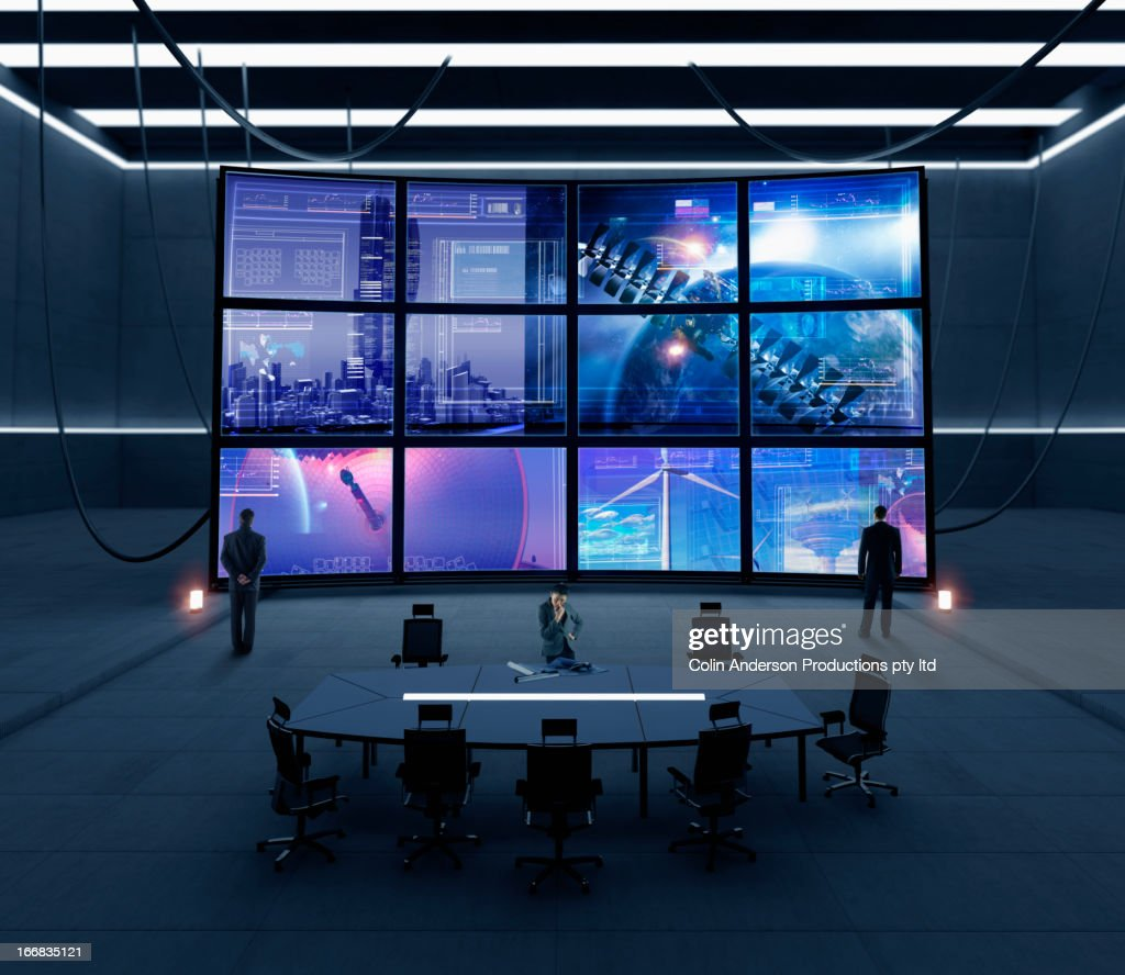 Business people watching screens in conference room : Stock Photo