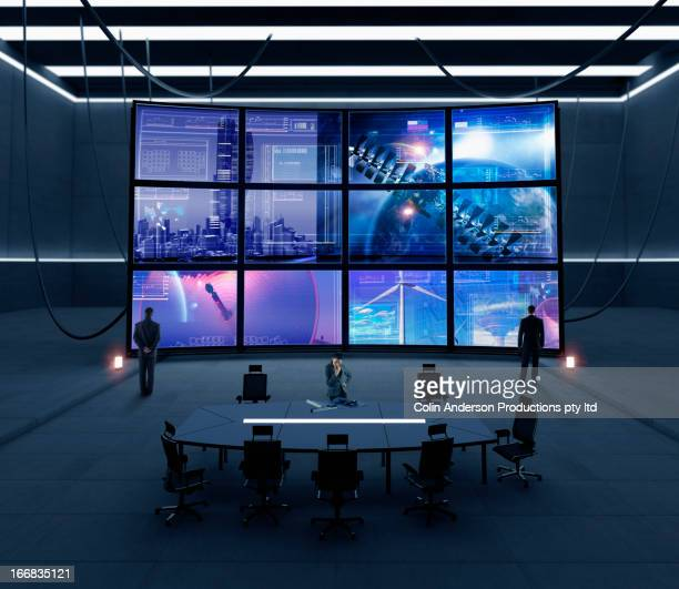 business people watching screens in conference room - spionage en toezicht stockfoto's en -beelden