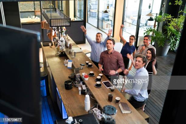 business people watching sport on television - medium group of people stock pictures, royalty-free photos & images