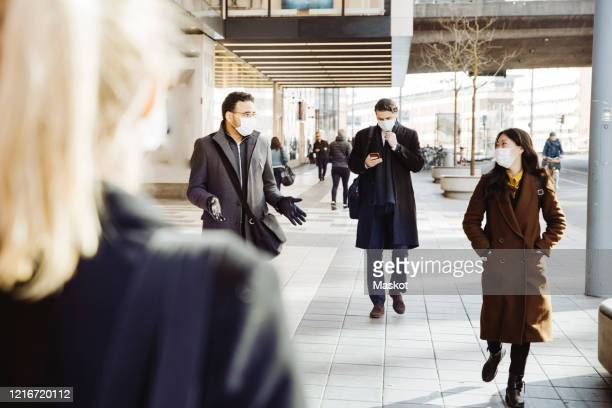business people wearing face mask walking in street - social distancing stock pictures, royalty-free photos & images