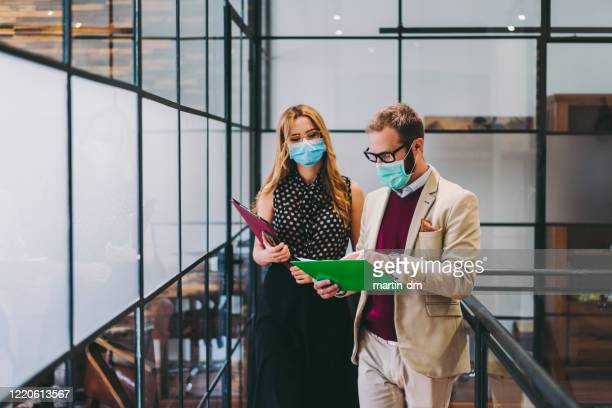 business people wearing face masks at work during covid-19 pandemic - prevention imagens e fotografias de stock