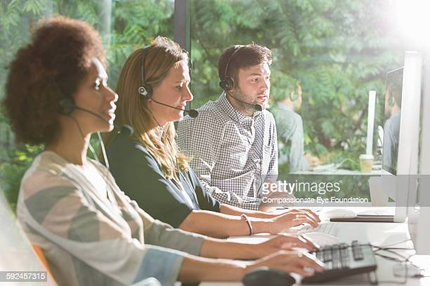 Business people wearing headsets in office