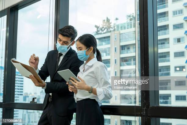 business people wearing protective face mask and having discussion with his assistants in office. - employee engagement stock pictures, royalty-free photos & images