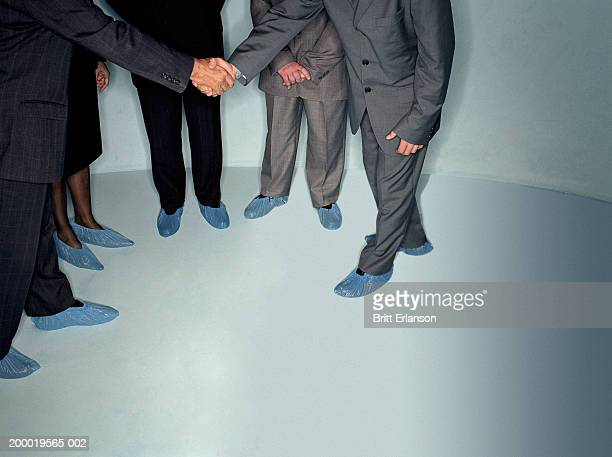 business people wearing shoe protectors, two men shaking hands - shoe covers stock pictures, royalty-free photos & images
