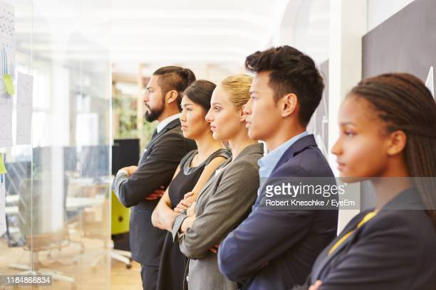 business people with arms crossed standing in office - five people stock pictures, royalty-free photos & images