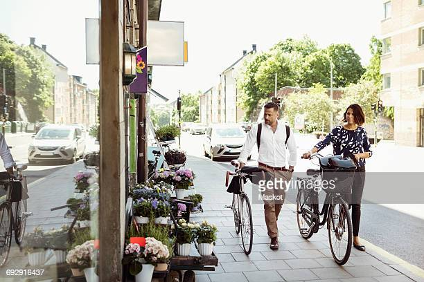 Business people with bicycles walking on sidewalk in city