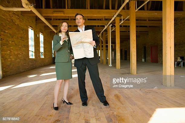 Business People with Blueprints in an Empty Loft