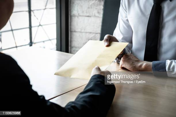 business people with bribe at desk in office - corruption stock pictures, royalty-free photos & images