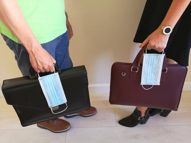 Business people with briefcases and a surgical masks at office