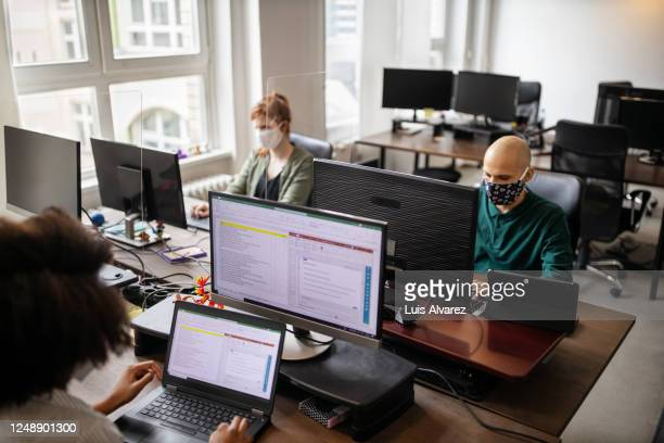 business people with face mask working in startup office - open plan stock pictures, royalty-free photos & images