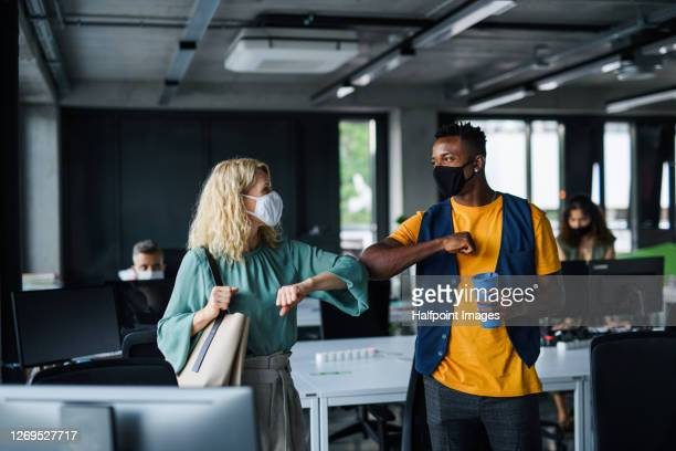 business people with face masks indoors in office, greeting. - elbow bump stock pictures, royalty-free photos & images