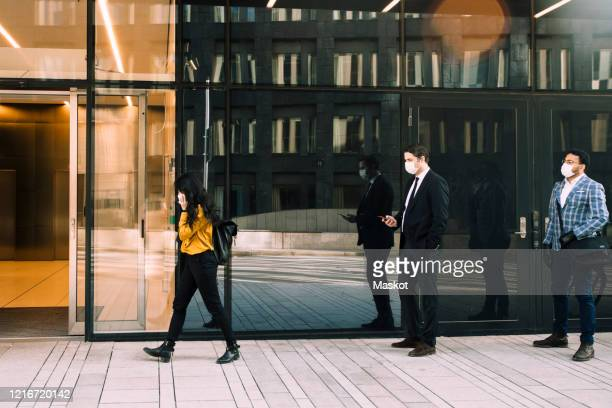 business people with face masks standing in line outside office building - social distancing stock pictures, royalty-free photos & images