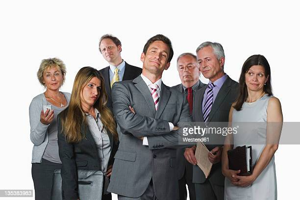 Business people with file, diary, mobile phone and newspaper against white background