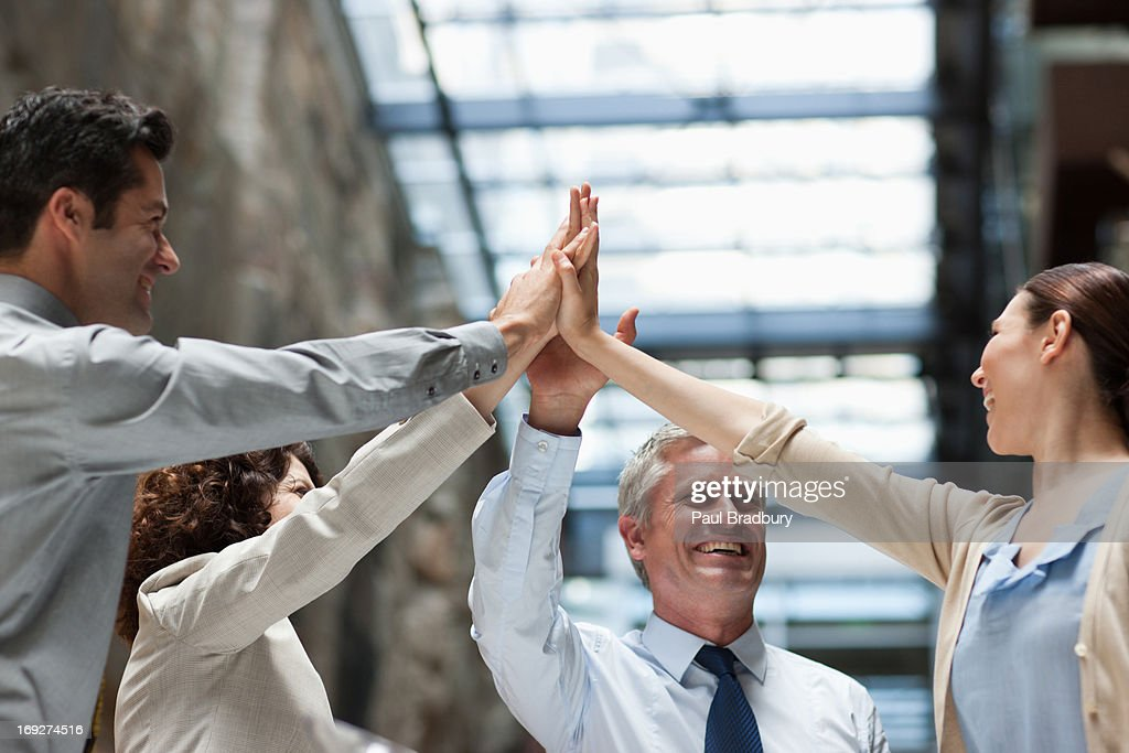 Business people with hands together : Stock Photo