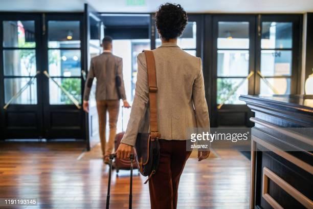 uomini d'affari con bagagli che lasciano l'hotel - leaving foto e immagini stock