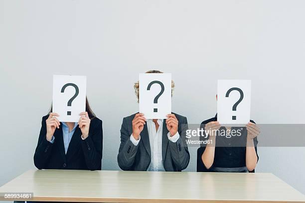 business people with question mark on placards - signo de interrogación fotografías e imágenes de stock