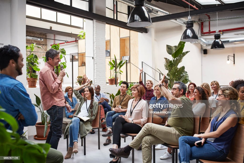 Business people with raised arms during seminar : Stock Photo