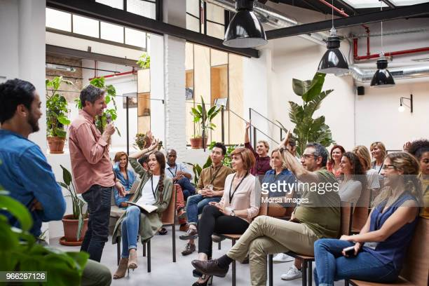business people with raised arms during seminar - formation photos et images de collection