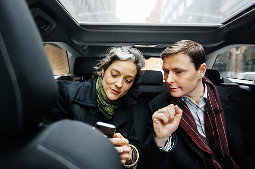 Business People with smart phone inside taxi - gettyimageskorea