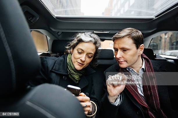 Business People with smart phone inside taxi