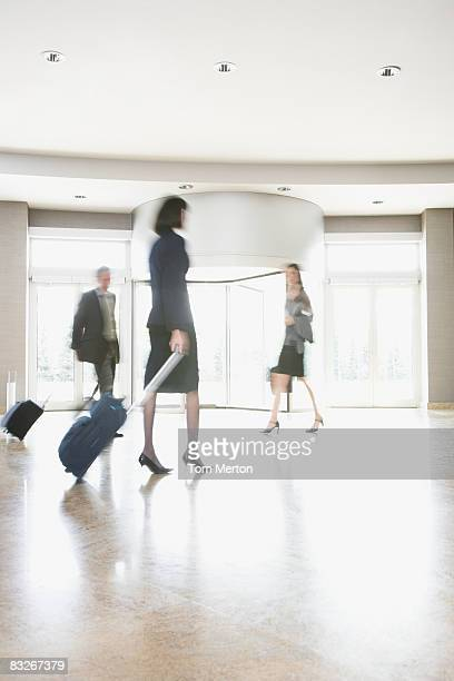 Business people with suitcases walking in lobby