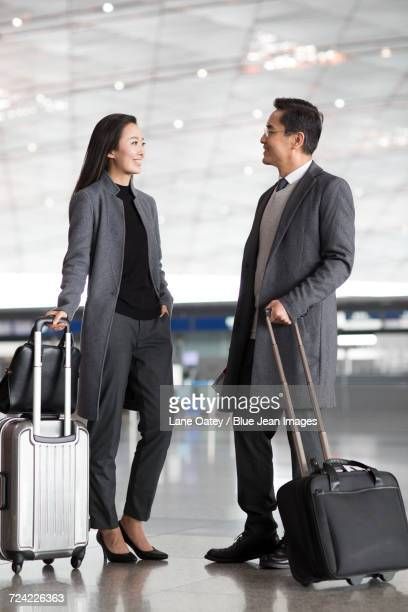 Business people with wheeled luggage in airport lobby
