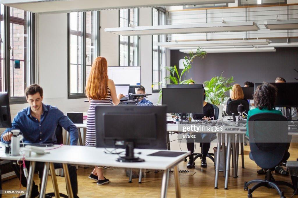 Geschäftsleute, die in einem geschäftigen, offenen Büro arbeiten : Stock-Foto
