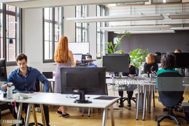 business people working at a busy open plan office - office imagens e fotografias de stock