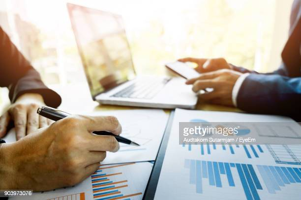 business people working at desk in office - business strategy stock photos and pictures