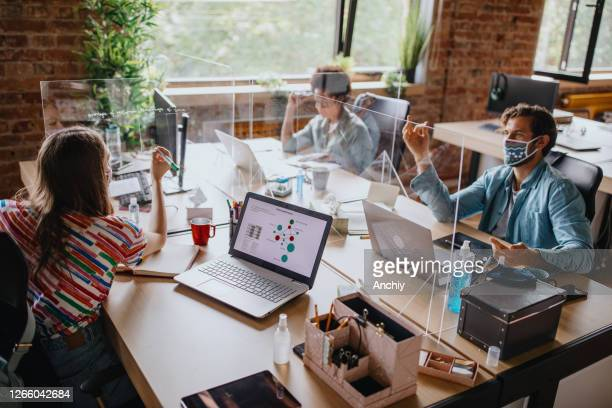 business people working at their desks with plexiglass panels in between them - new normal concept stock pictures, royalty-free photos & images