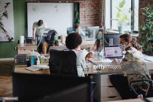 business people working at their desks with plexiglass panels in between them - epidemic stock pictures, royalty-free photos & images