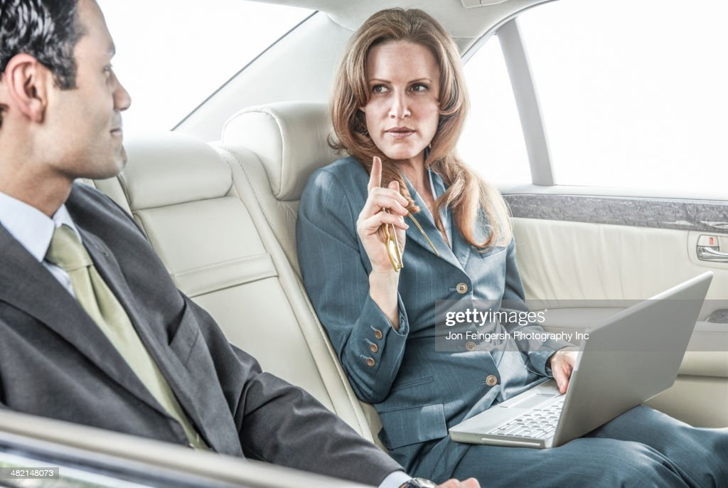 Business people working in backseat of car : Stock Photo