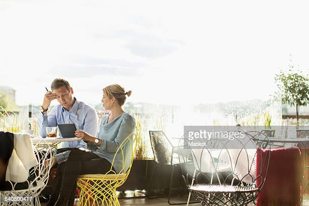 Business people working in cafe against clear sky