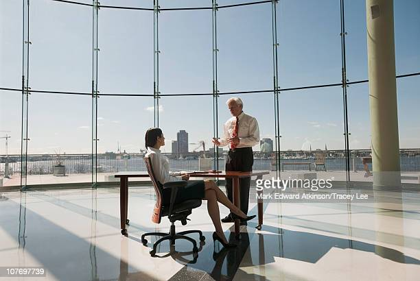 Business people working in large office with glass wall